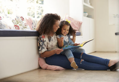 Woman and child reading book inside and smiling